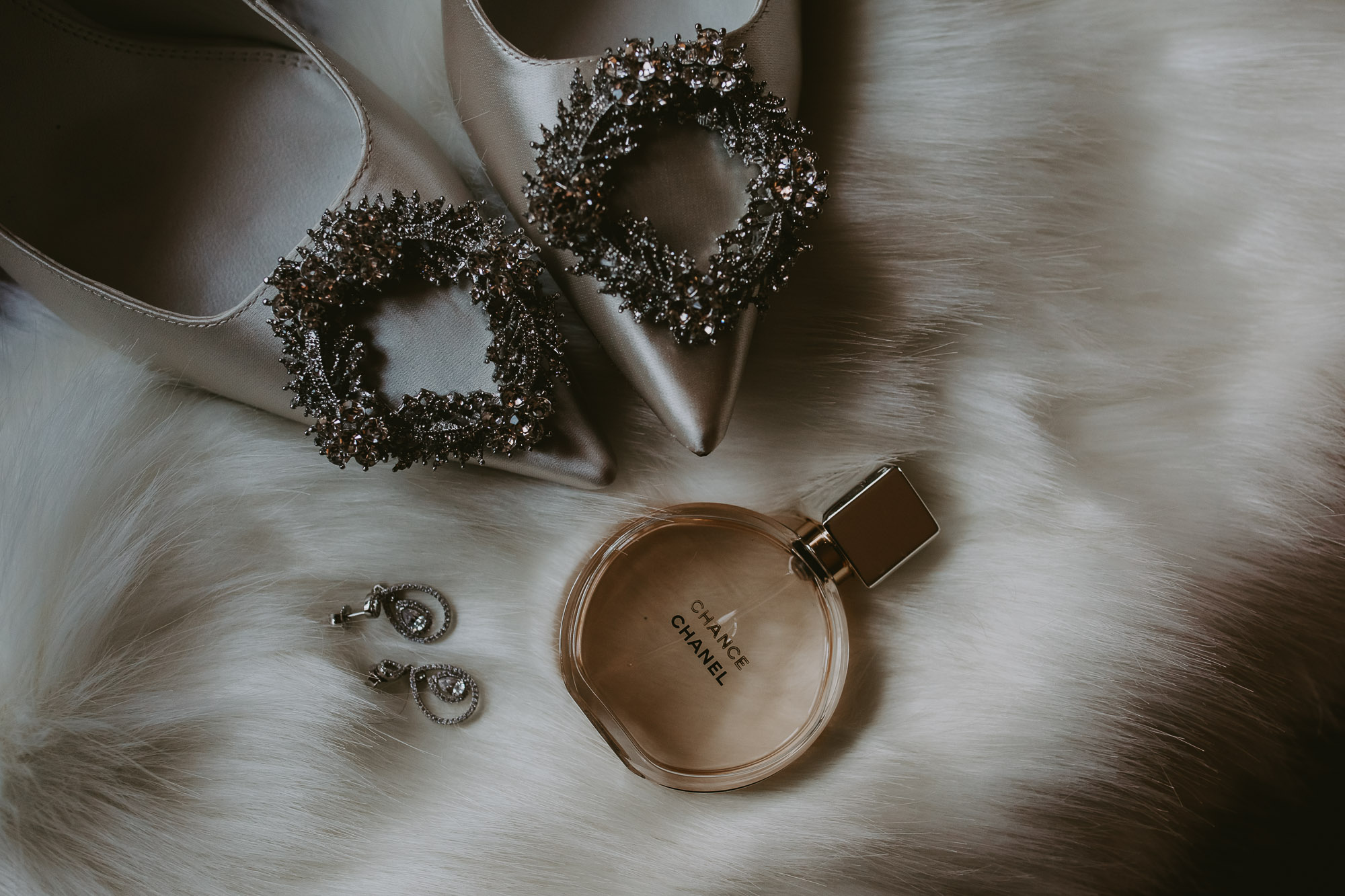 Wedding accessories, close up of Manolo Blahnik Hangisi bridal shoes, Chance Chanel perfume, earrings, white winter boleros