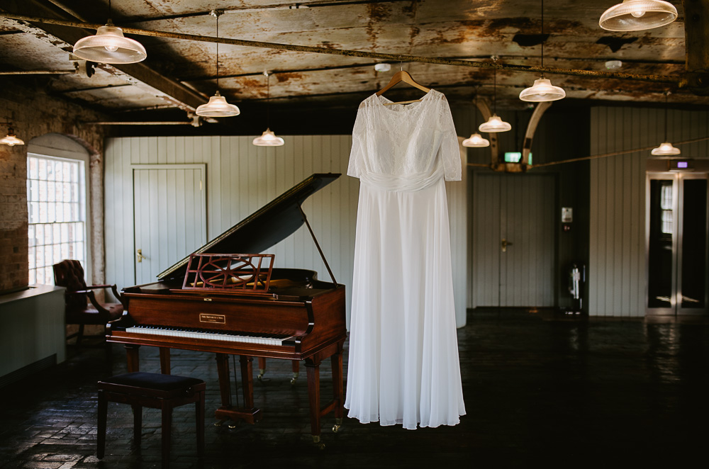 Wedding dress hanging up by piano