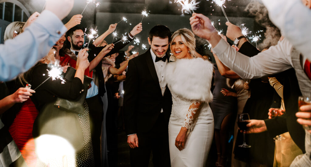 Bride and groom walk through sparkler exit on wedding day at Clonabreany House in Ireland