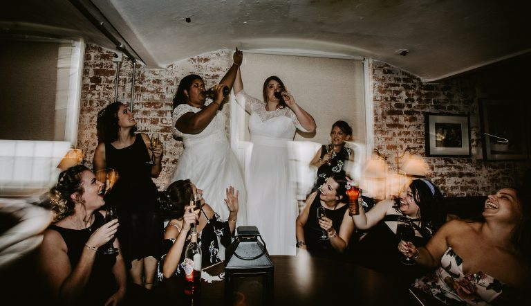 Two brides drinking on a table at West Mill Derby