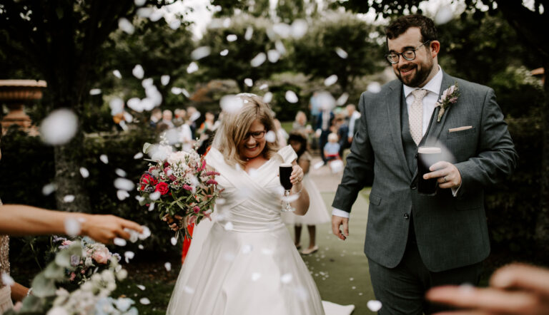Bride and groom walk down aisle as newlyweds drinking Guinness with confetti thrown in the air