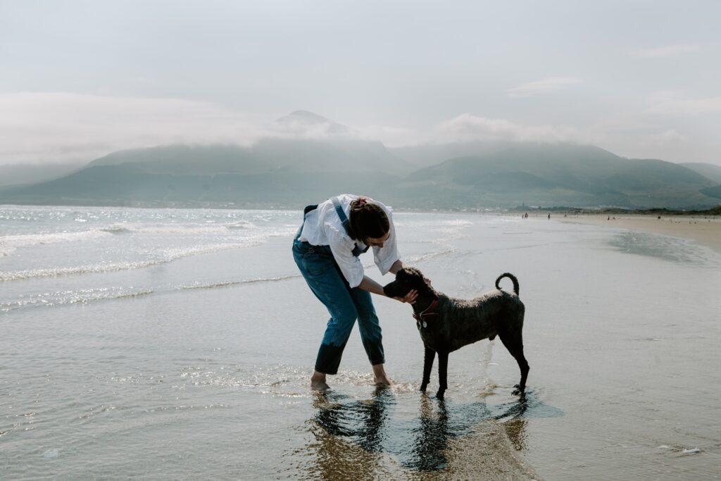 woman pets her dog at murlough beach