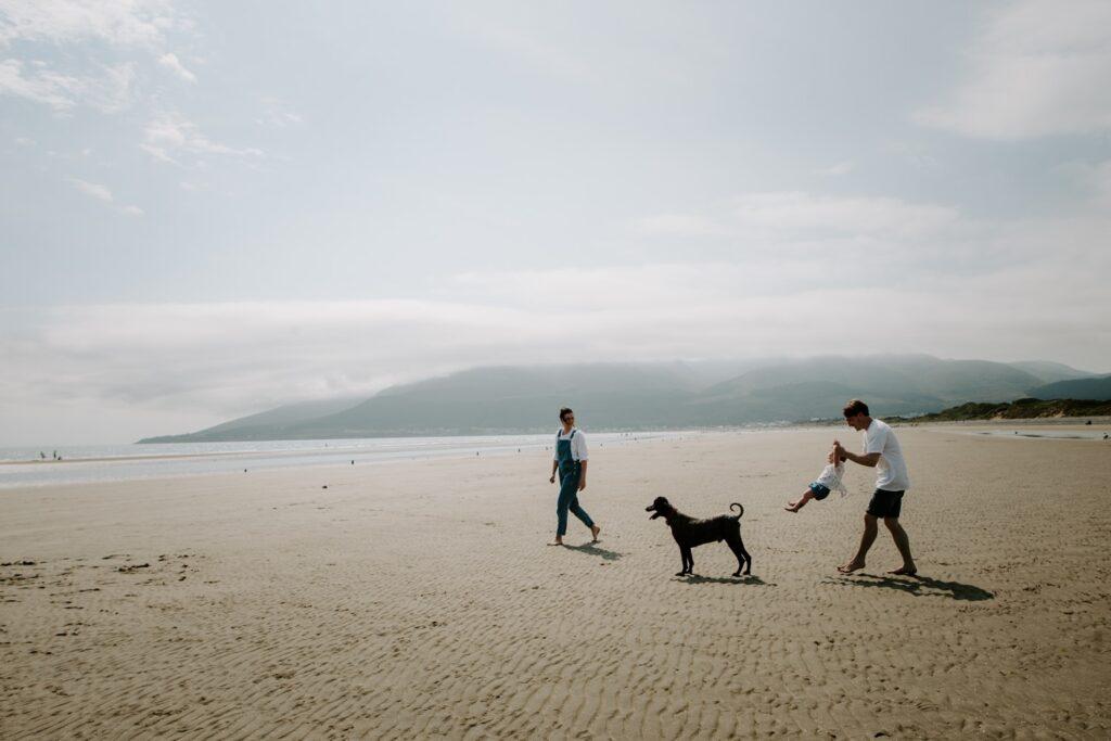 family walk on beach with pet dog at murlough beach