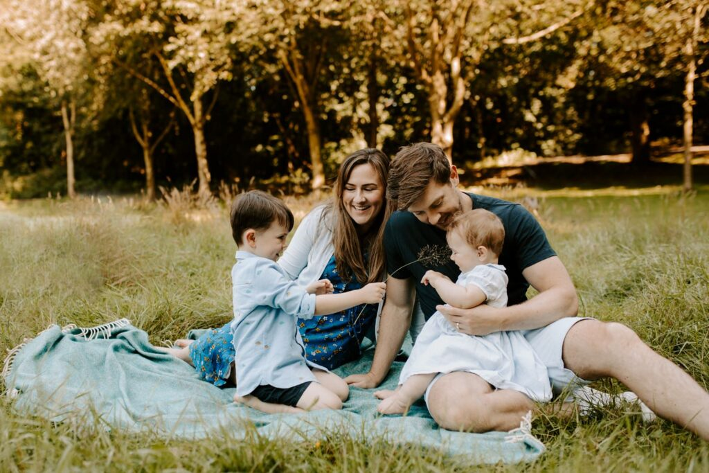 outdoor family portrait, mum , dad and two kids on picnic blanket