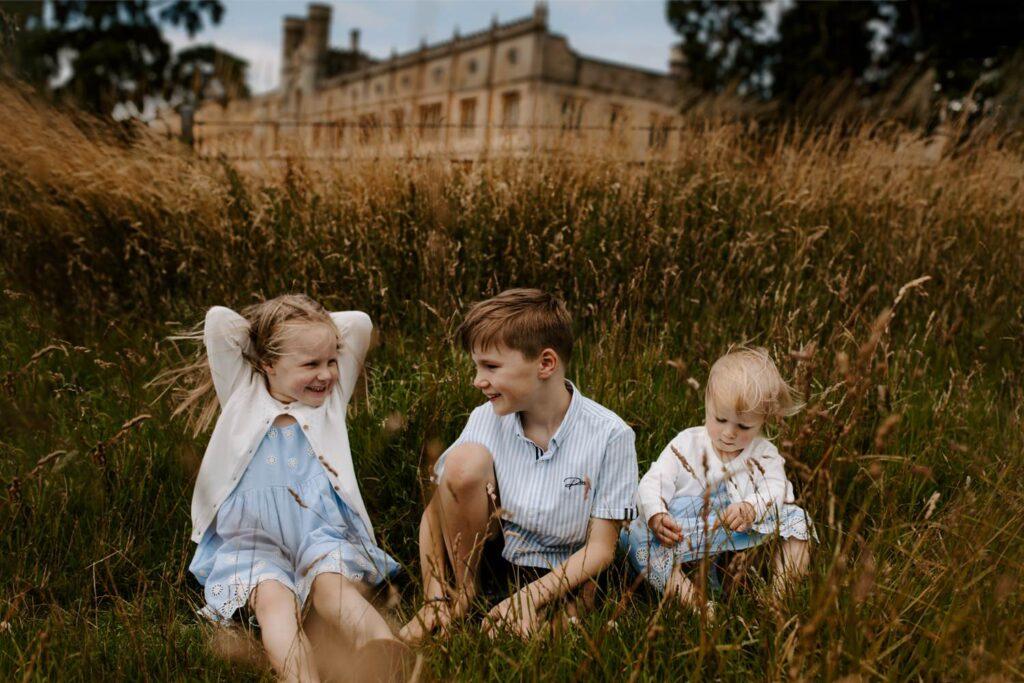 three children siblings sit in field infront of Ashton Court, Bristol