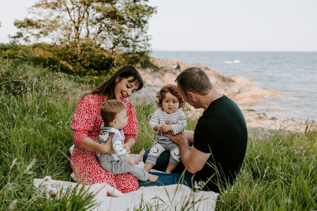 outdoor family portrait, mum , dad and twin babies on picnic blanket