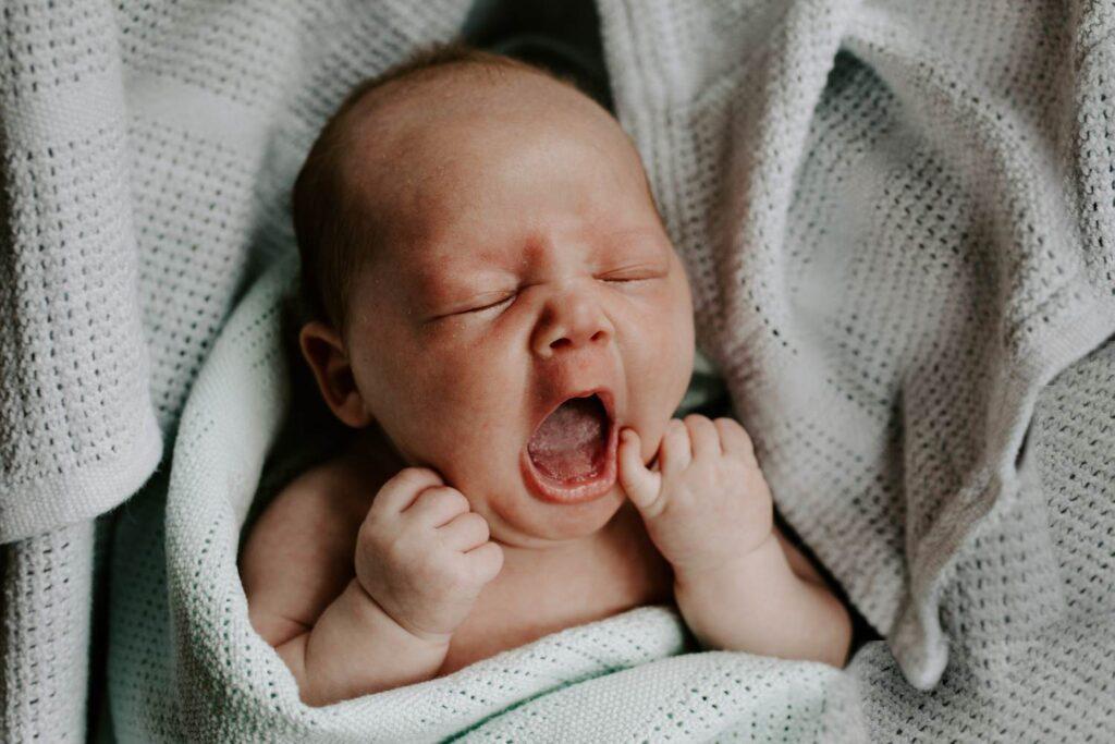 newborn boy yawning in baby blanket, northern ireland family portraits