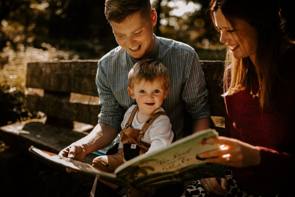 mum and dad read book to son outside